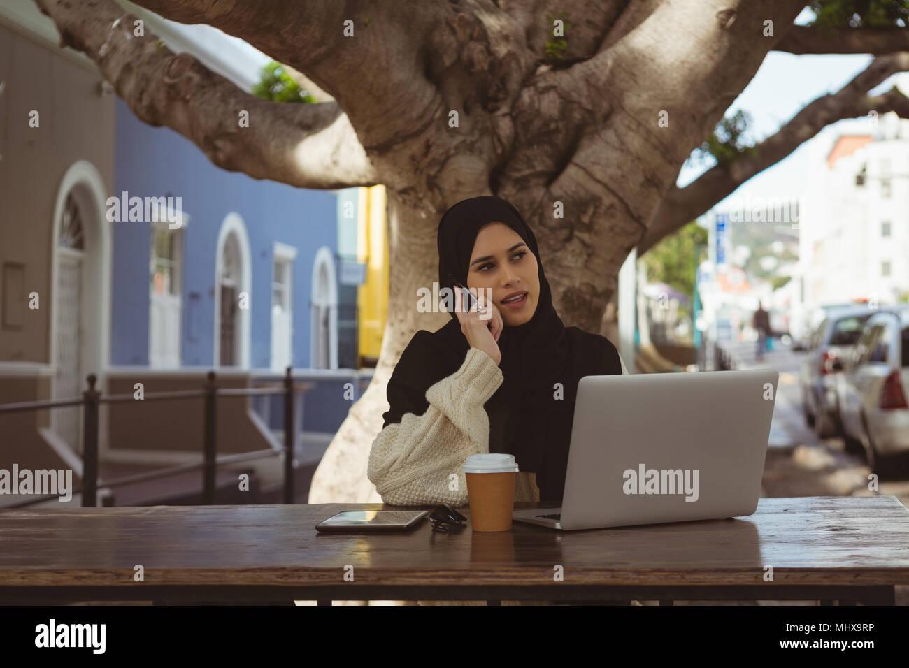 Urban hijab woman talking on mobile phone at cafe - Stock Image