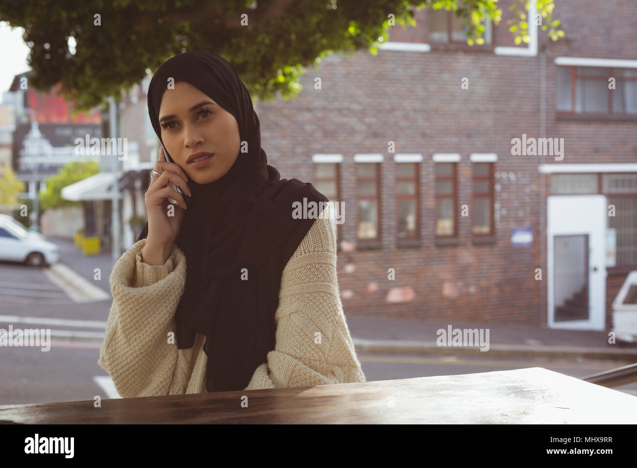 Urban hijab woman talking on mobile phone at cafe - Stock Image