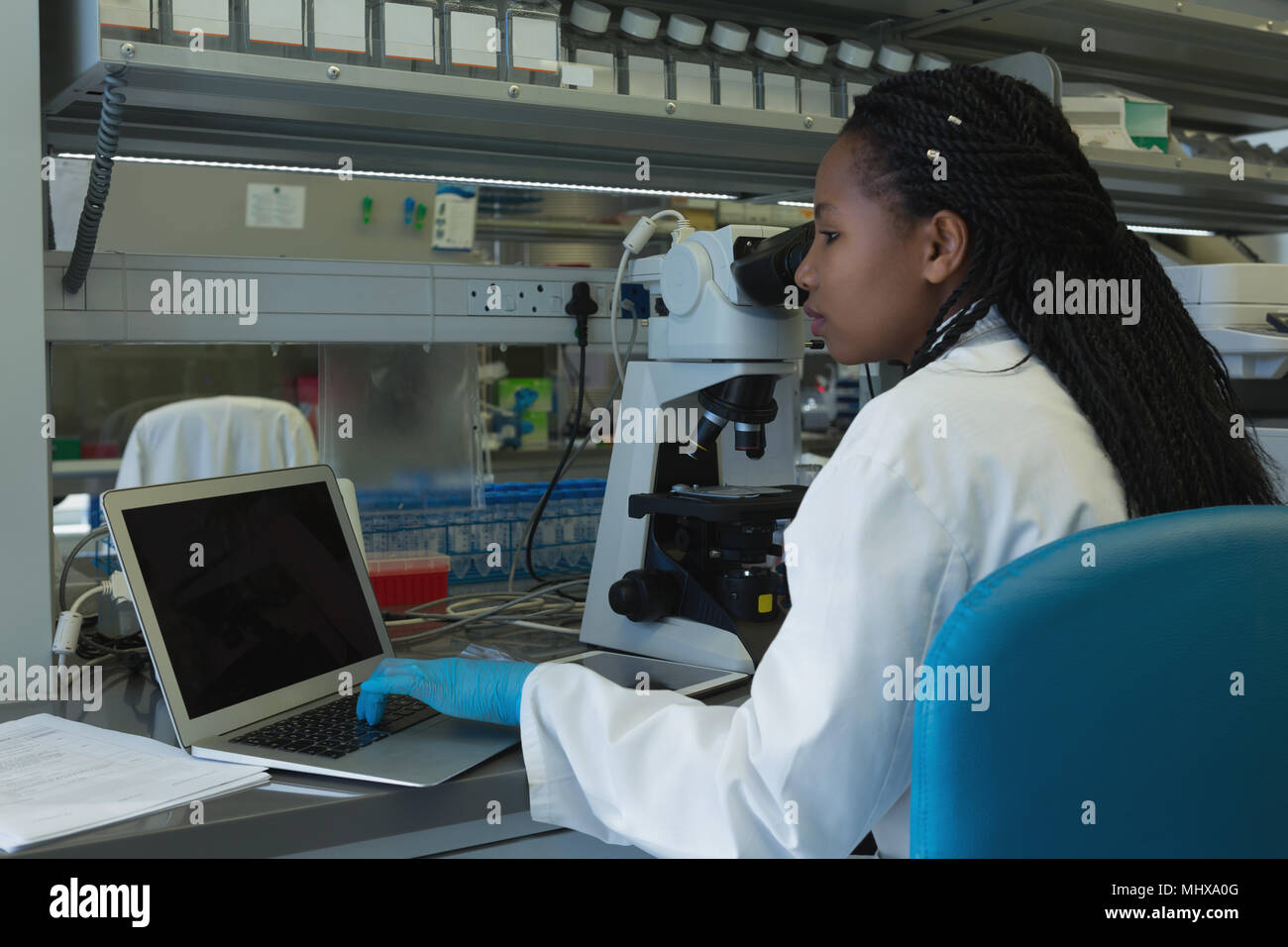 Scientist using laptop at desk - Stock Image