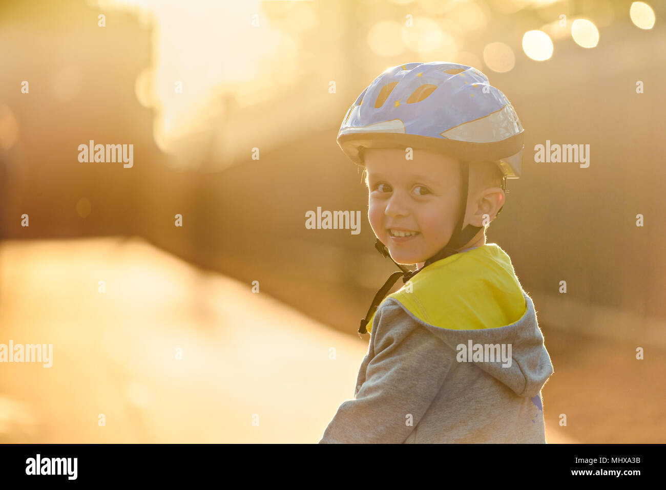 Smiling aussie boy wearing helmet and riding his bicycle a day in Glenelg, South Australia - Stock Image