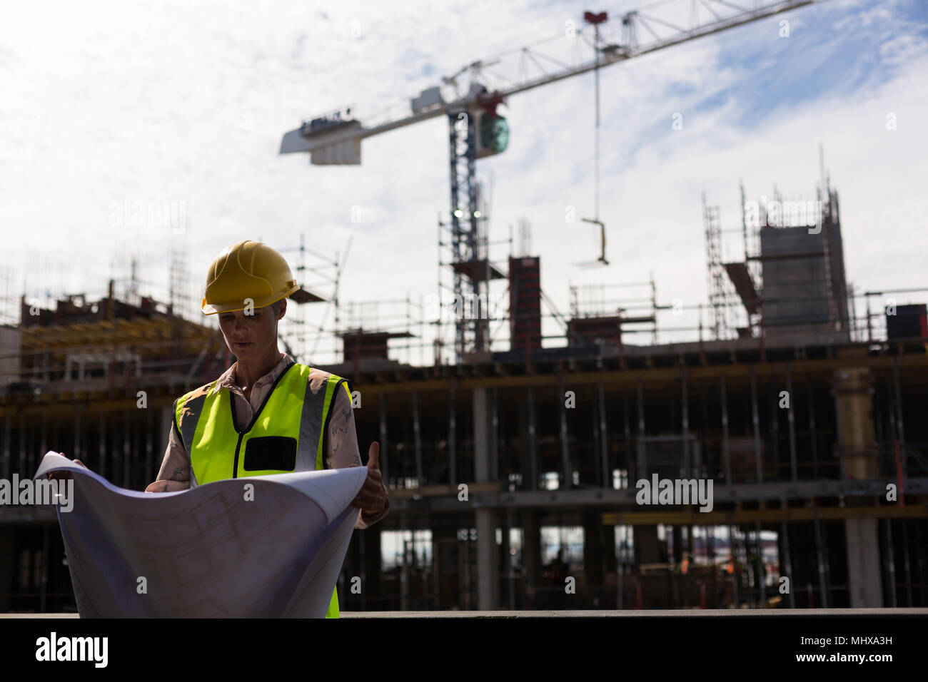 Female architect checking blueprint - Stock Image
