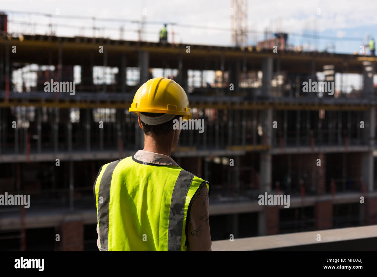 Female architect standing at construction site - Stock Image