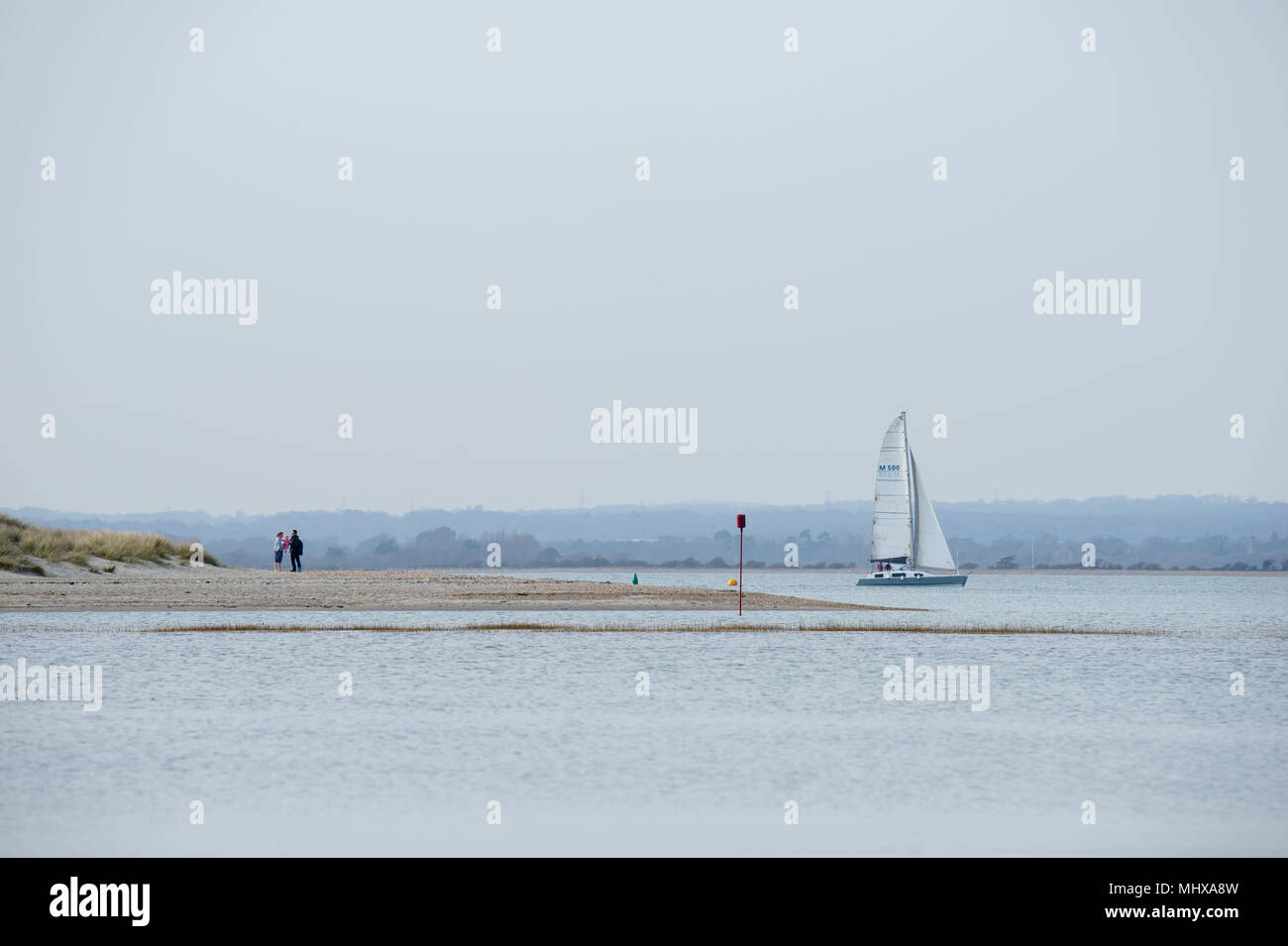a young couple with their baby on the spit or Hoe at West Wittering with a yacht sailing in the background on a sunny cloudless day with the West down - Stock Image