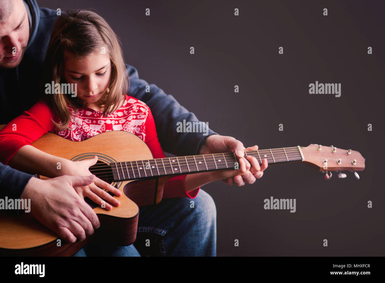 Father teaching daughter to play guitar Stock Photo