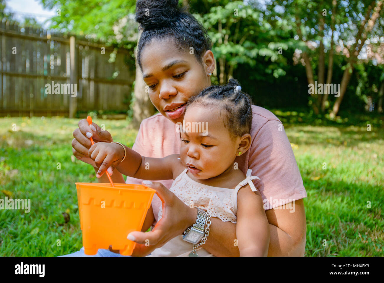 Mid adult woman playing with toy bucket in garden with baby daughter - Stock Image