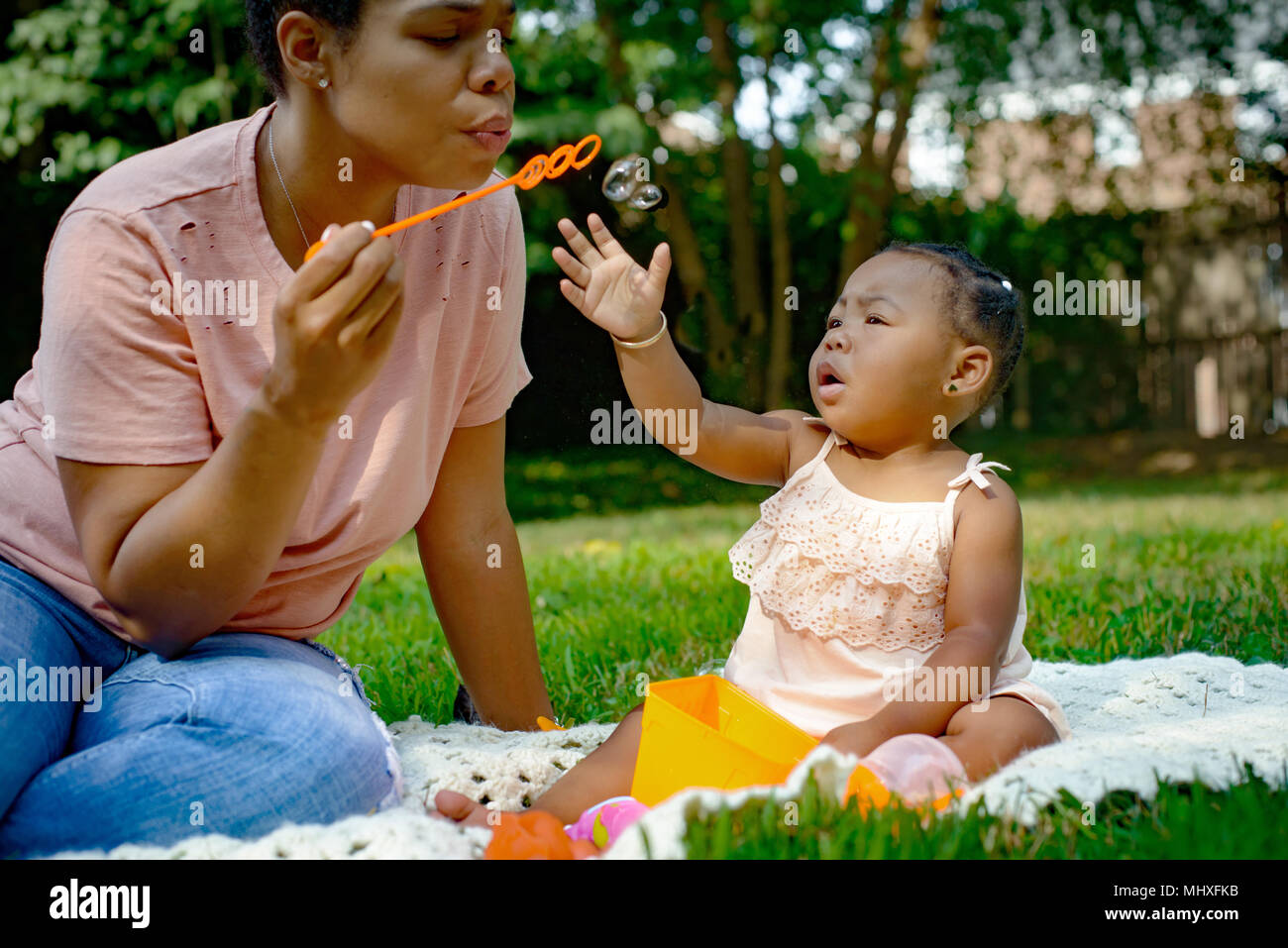 Mid adult woman blowing bubbles in garden for baby daughter - Stock Image