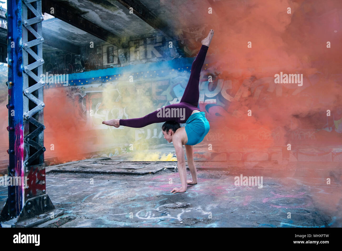 Girl practising yoga on outdoor stage - Stock Image