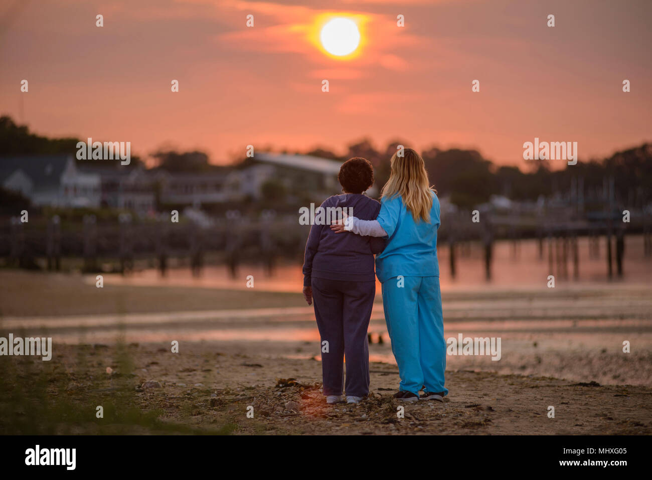 Woman and carer enjoying evening sunset by sea - Stock Image