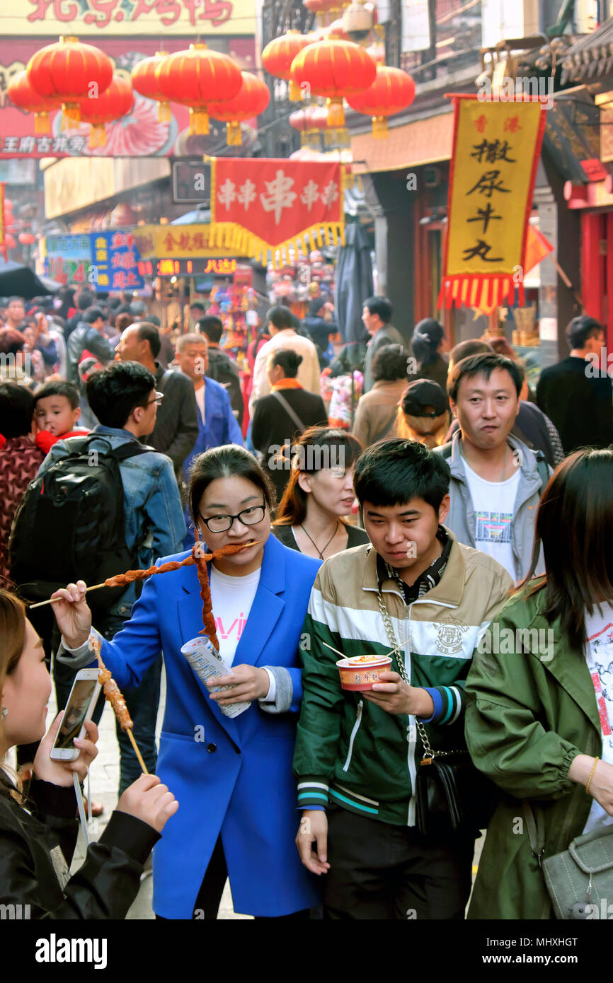 Locals eating skewers and other fast food, Wangfujing Snack Street, Dongcheng District, Beijing, China - Stock Image