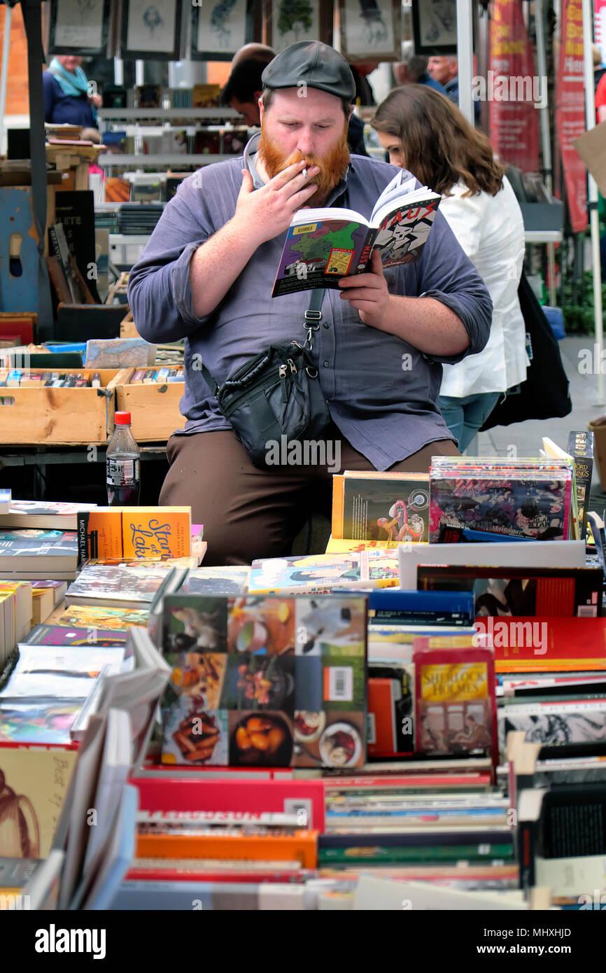 A smoking book seller at the Temple Bar Book Market, Temple Bar Square, Dublin, Ireland - Stock Image