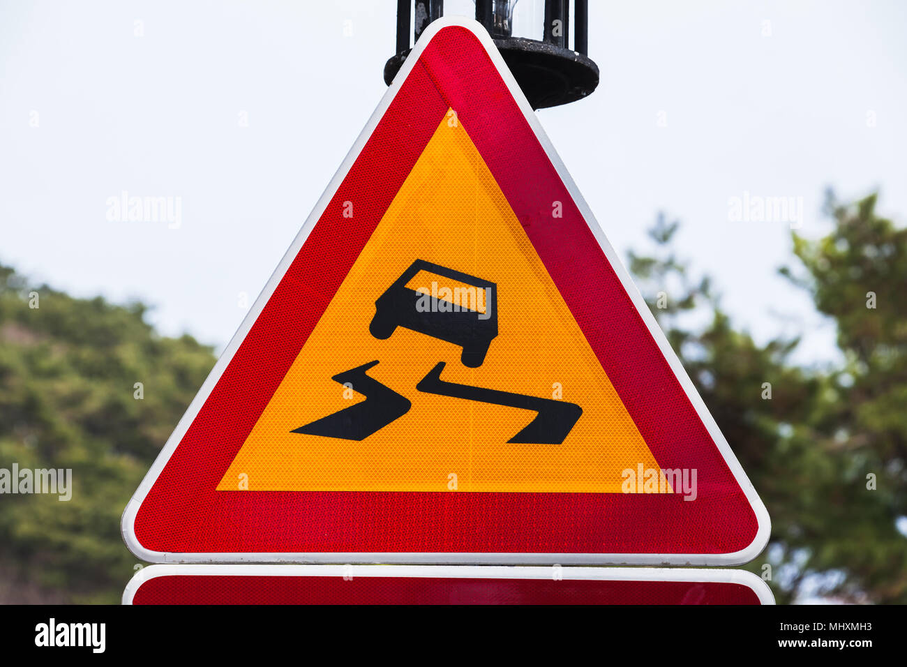 Slippery road, warning triangle road sign over bright sky background - Stock Image
