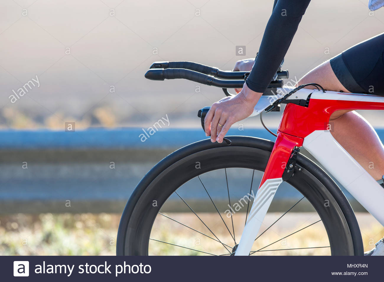 Close-up of female cyclist hands on handlebars of race bicycle - Stock Image
