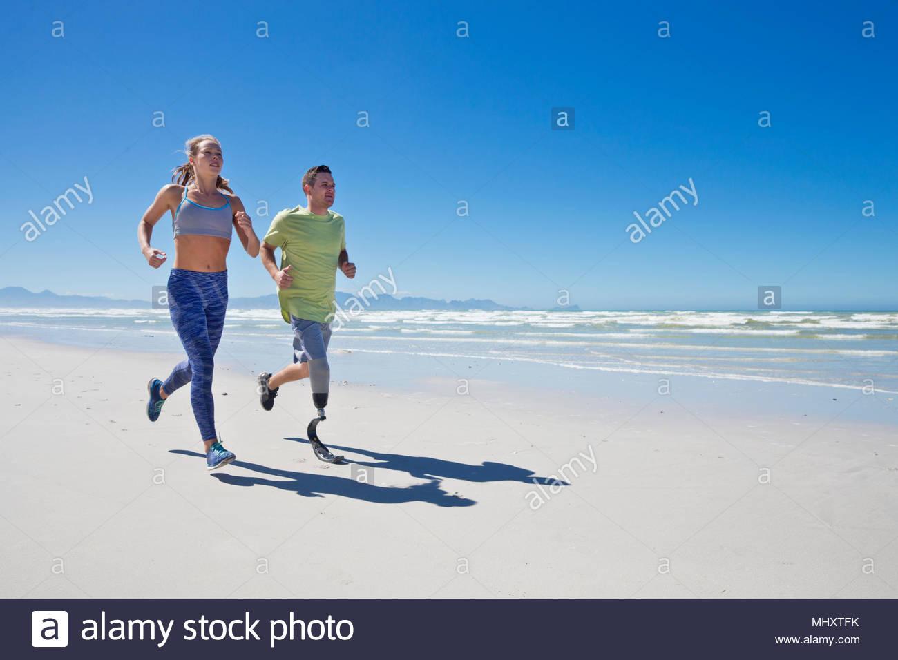 Man Wearing Prosthetic Blade Running Along Shoreline Of Beach With Female Partner - Stock Image