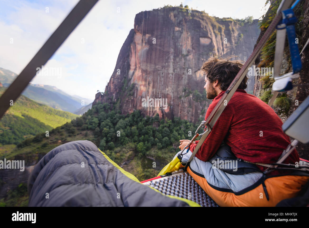 Rock climber on portaledge, looking at view, Liming, Yunnan Province, China - Stock Image