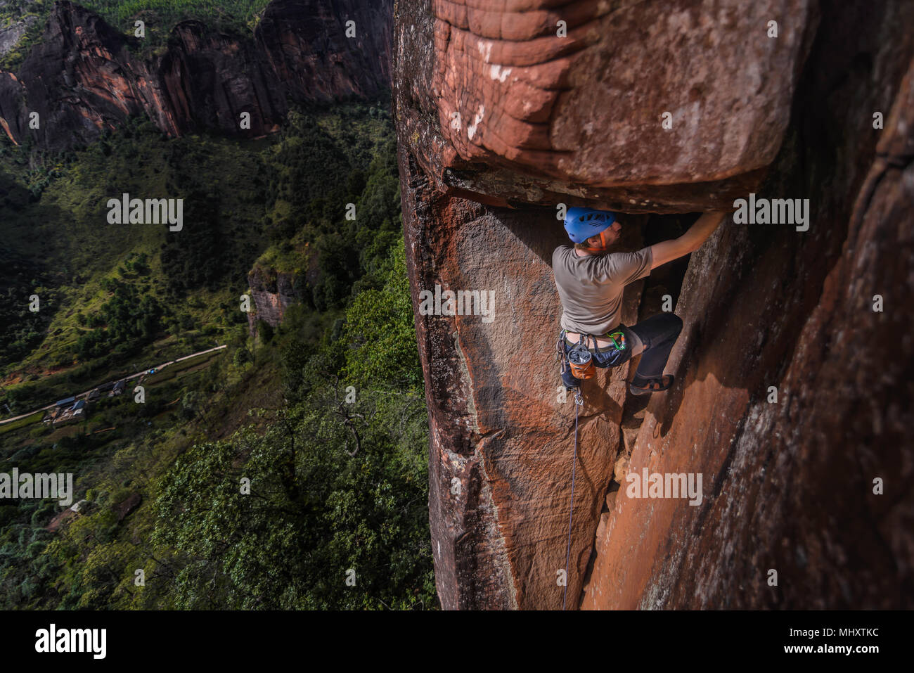 Rock climber climbing sandstone rock, elevated view, Liming, Yunnan Province, China - Stock Image