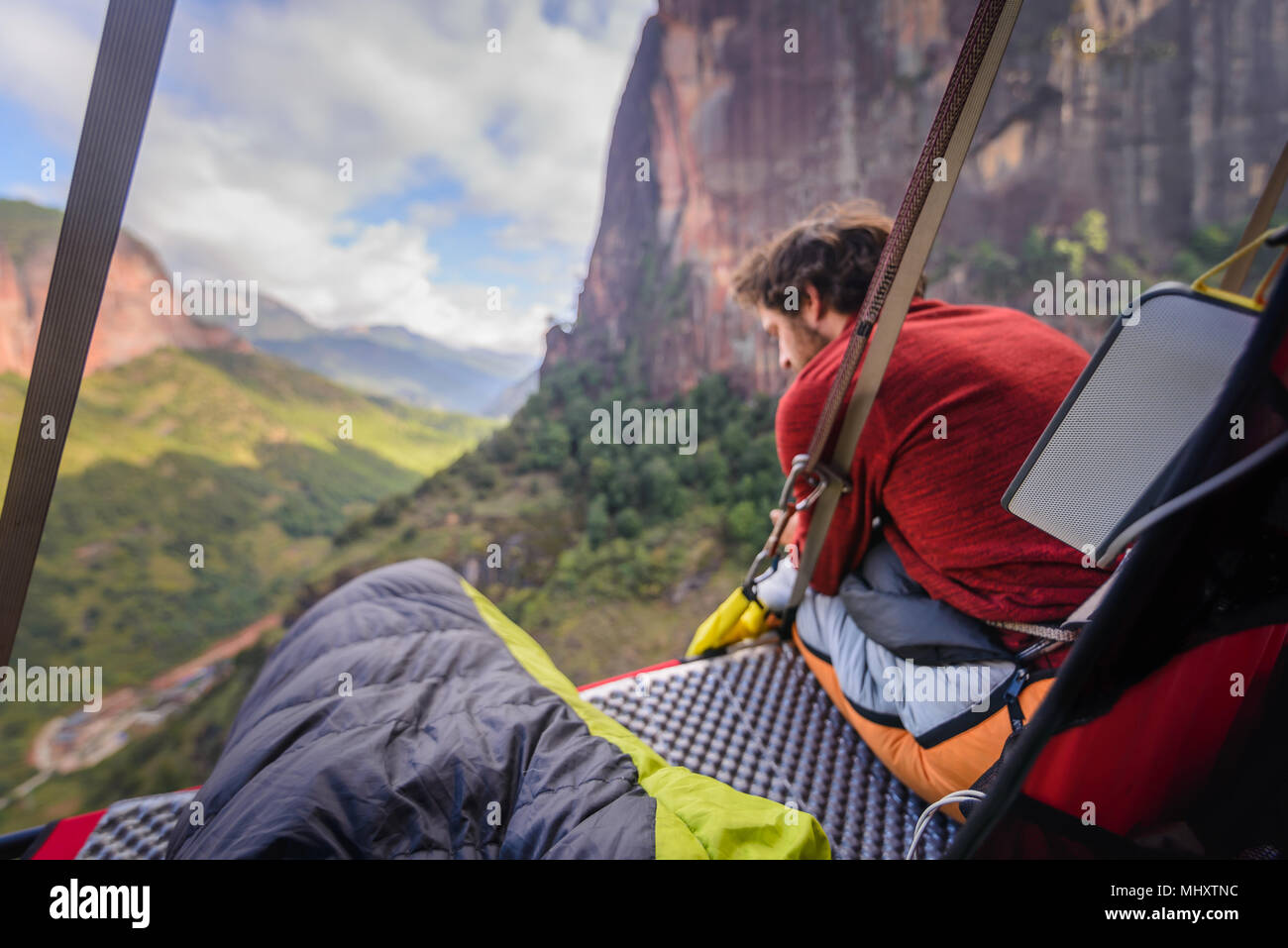 Rock climber sitting on portaledge, looking at view, Liming, Yunnan Province, China - Stock Image