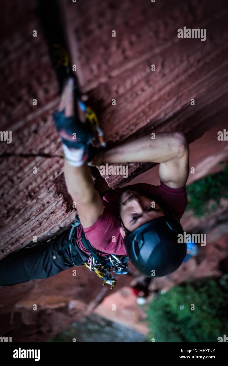 Rock climber climbing sandstone rock, overhead view, Liming, Yunnan Province, China - Stock Image