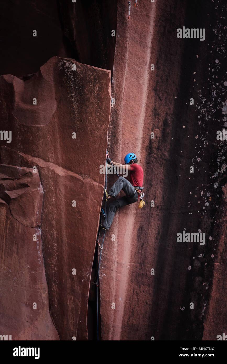 Rock climber climbing sandstone rock, Liming, Yunnan Province, China - Stock Image