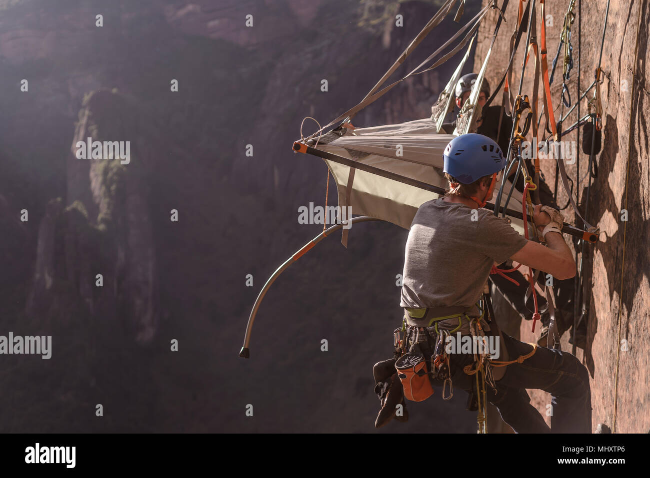 Two rock climbers attaching portaledge to rock, Liming, Yunnan Province, China - Stock Image