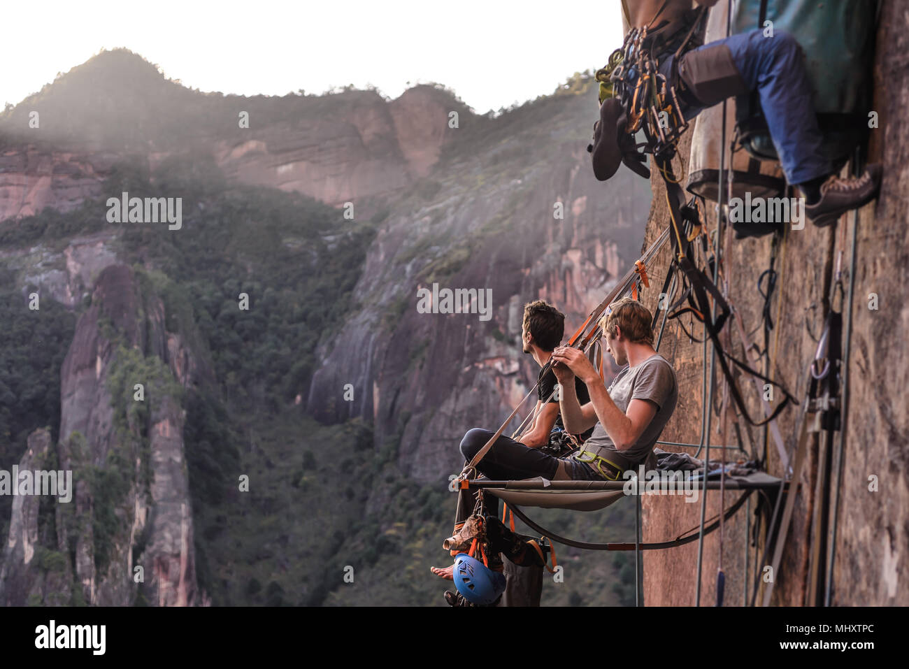 Two rock climbers sitting on portaledge, looking at view, Liming, Yunnan Province, China - Stock Image