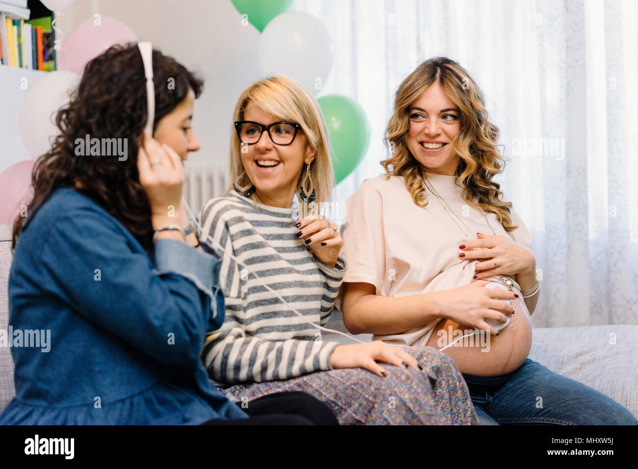 Pregnant woman and friends on sofa using prenatal listening device - Stock Image
