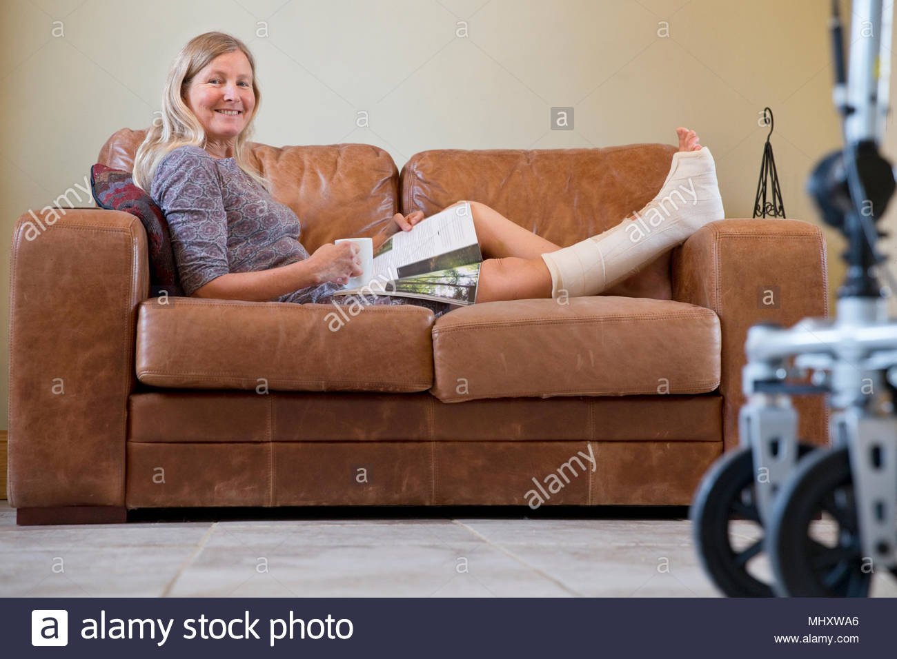Portrait Of Mature Woman With Leg In Plaster Cast Lying On Sofa At Home - Stock Image