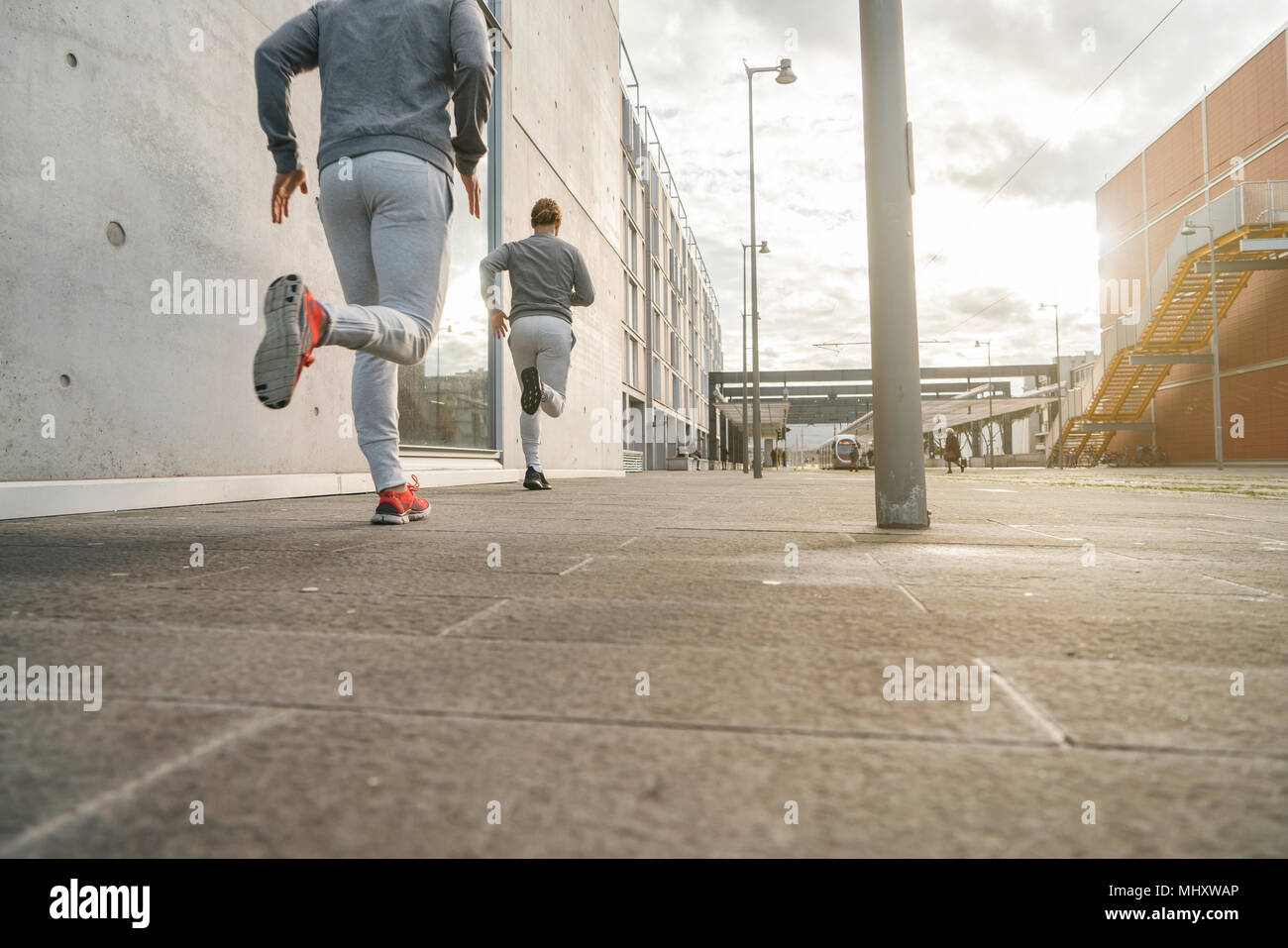 Young adult male twin runners, running along city sidewalk, rear view - Stock Image