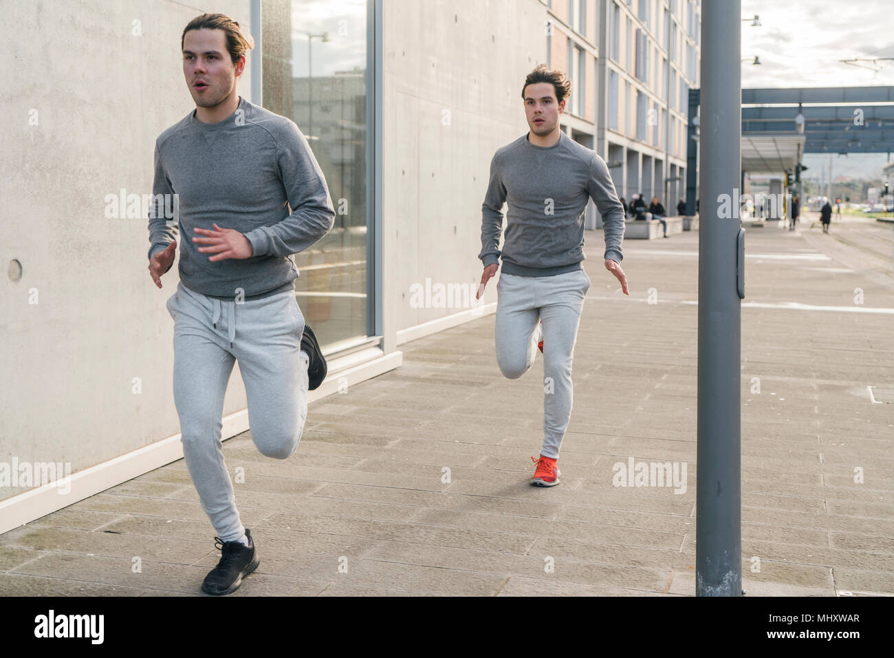 Young adult male twin runners, running along city sidewalk - Stock Image