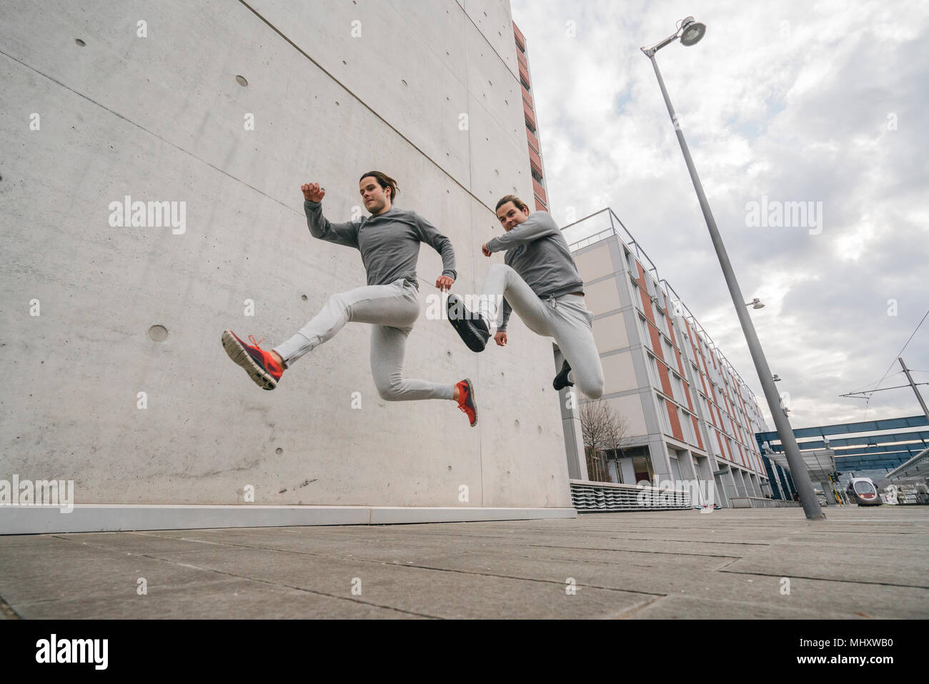 Young adult male twin runners, running and jumping mid air on city sidewalk - Stock Image