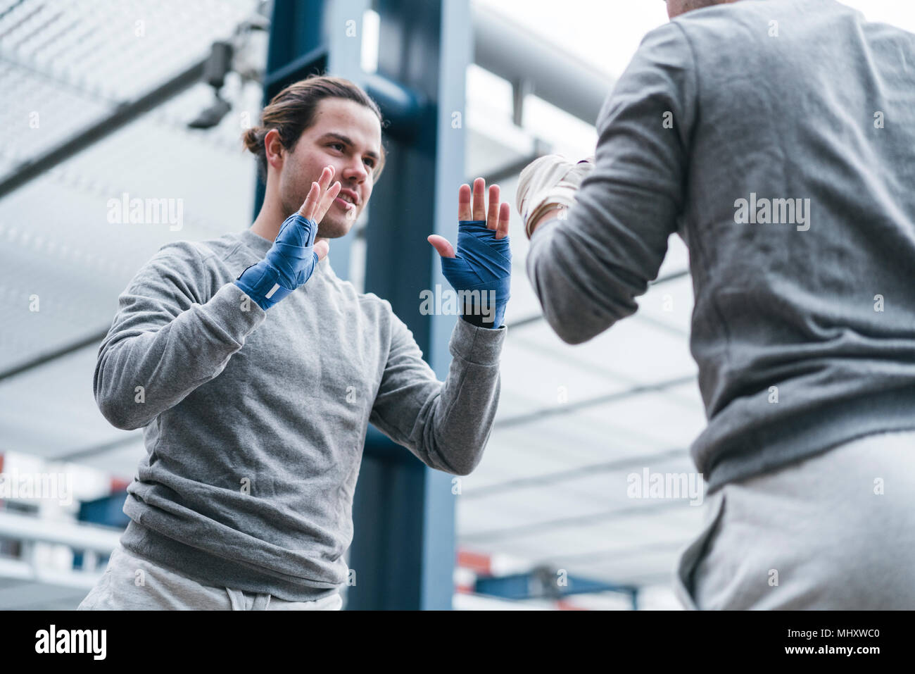 Identical male adult twin boxers training outdoors, practicing punches - Stock Image