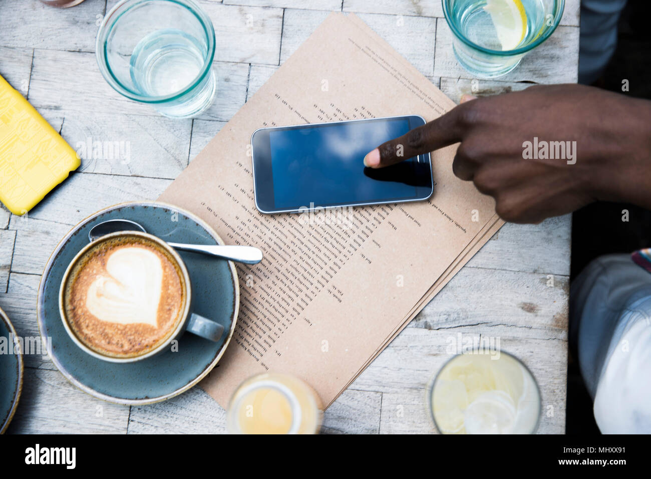 Coffee, mobile phone, menu on wooden table - Stock Image
