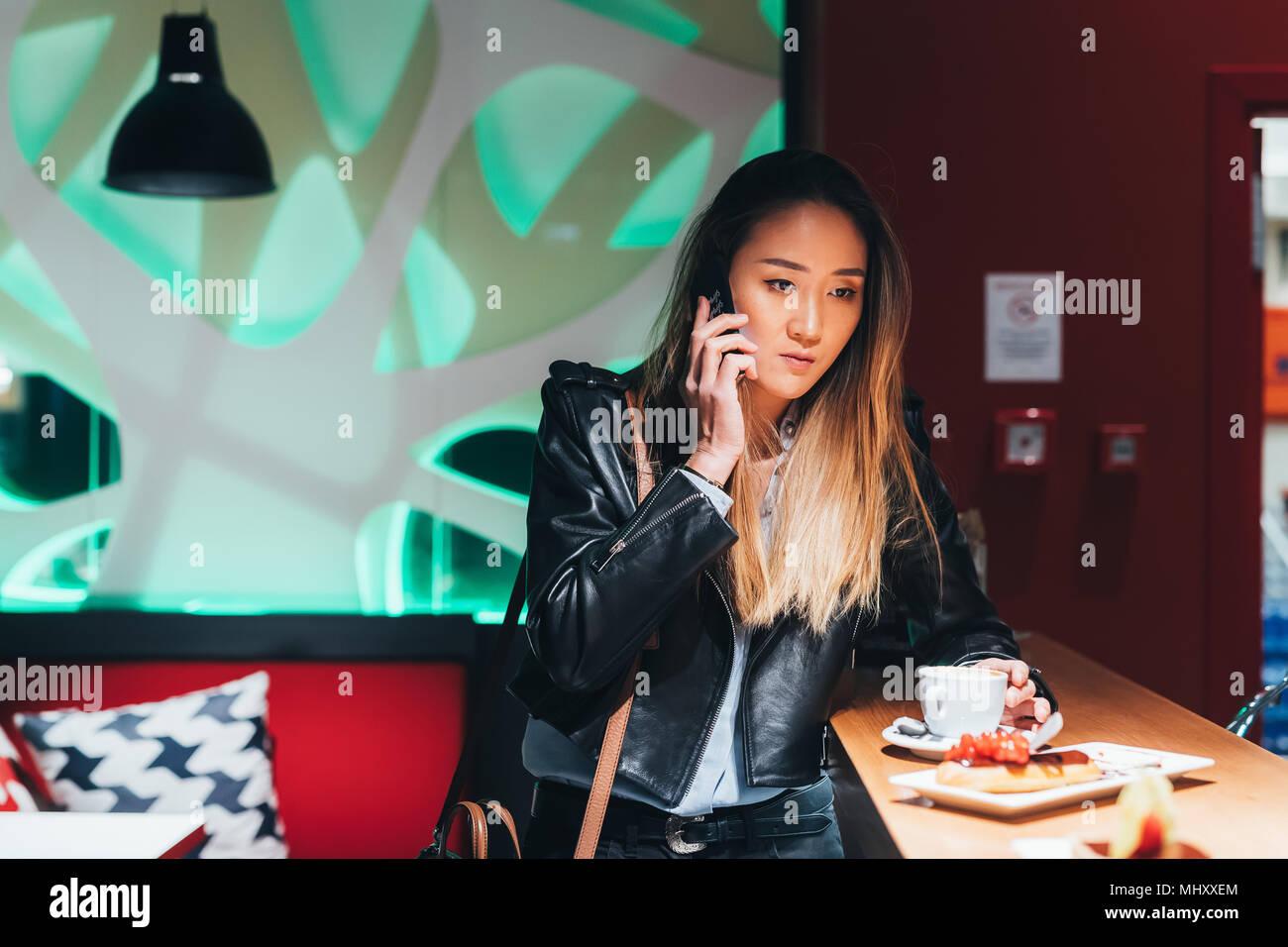 Woman sitting in bar, drinking coffee, using smartphone - Stock Image
