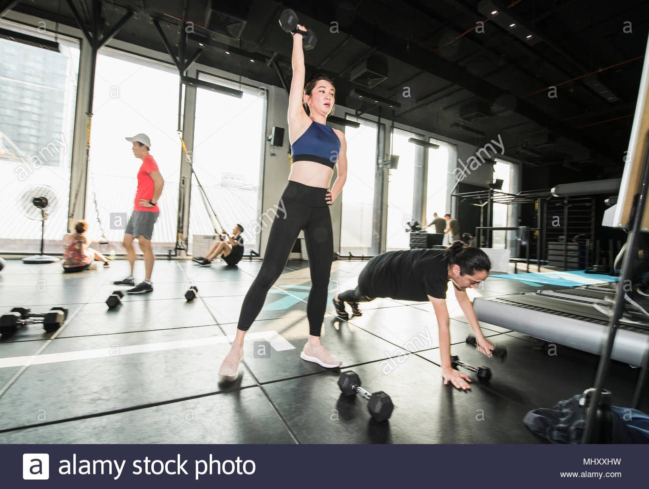 Group of people working out in gym, lifting weights - Stock Image