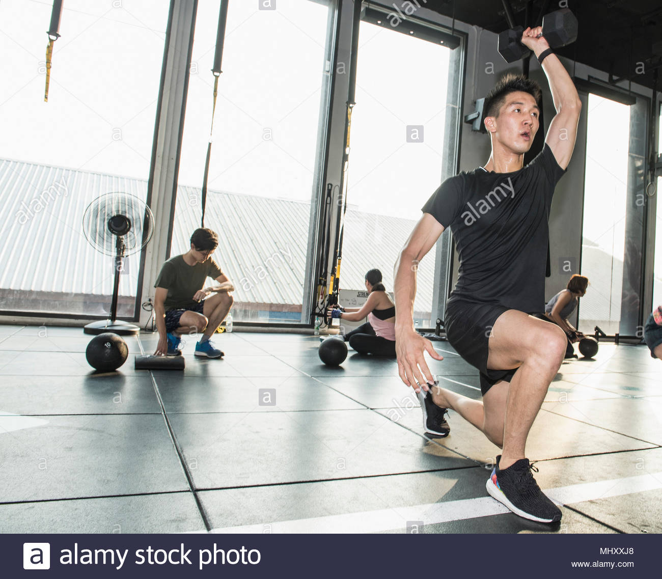 Group of people working out in gym, man in foreground lifting hand weights - Stock Image