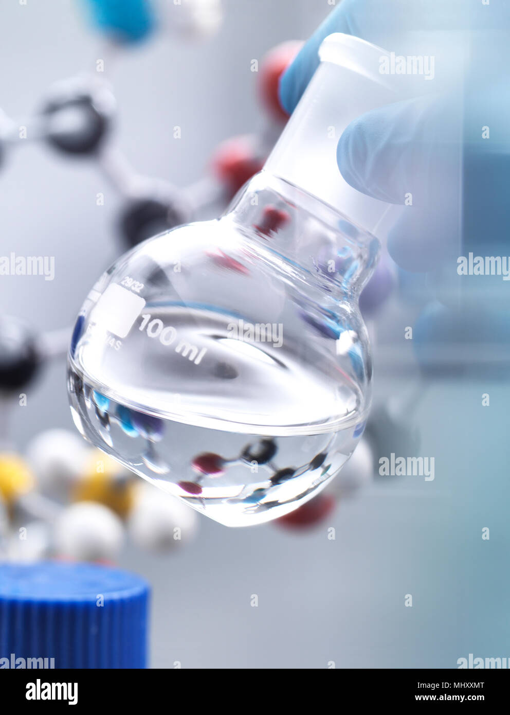 Scientist preparing chemical formula in a laboratory flask during an experiment, molecular model in the background - Stock Image