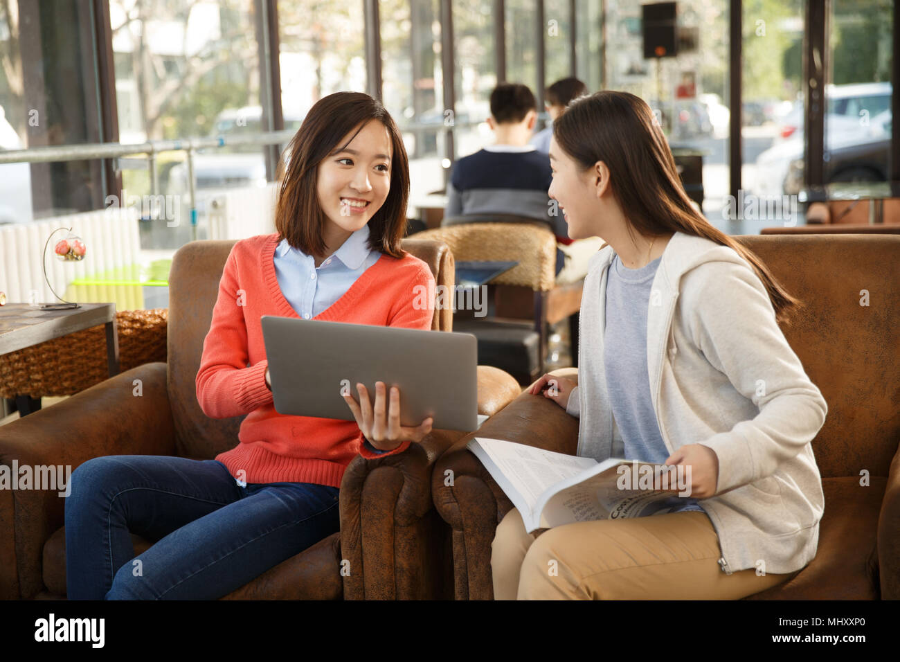 Young women study in coffee shop - Stock Image