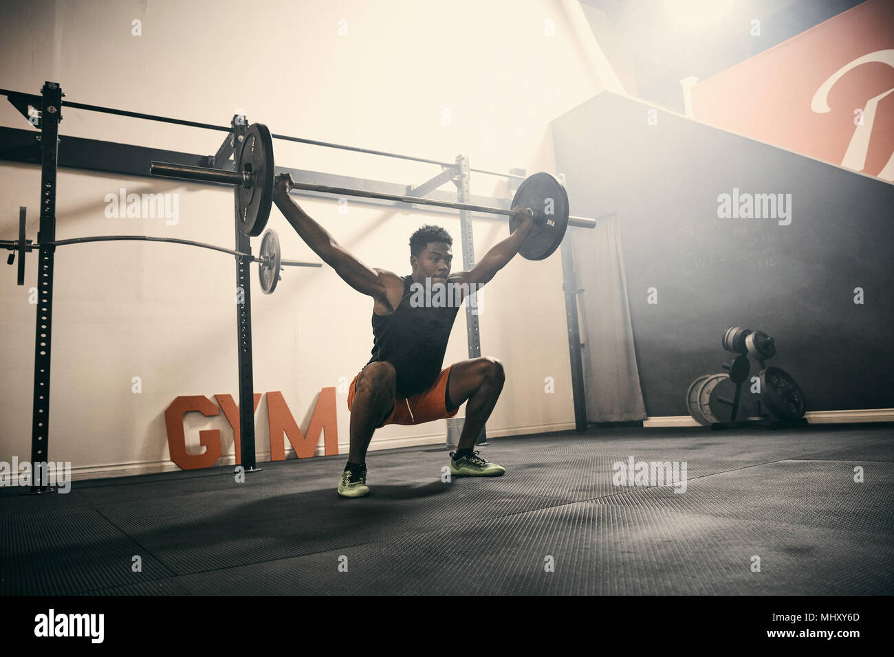 Man in gym weightlifting using barbell - Stock Image