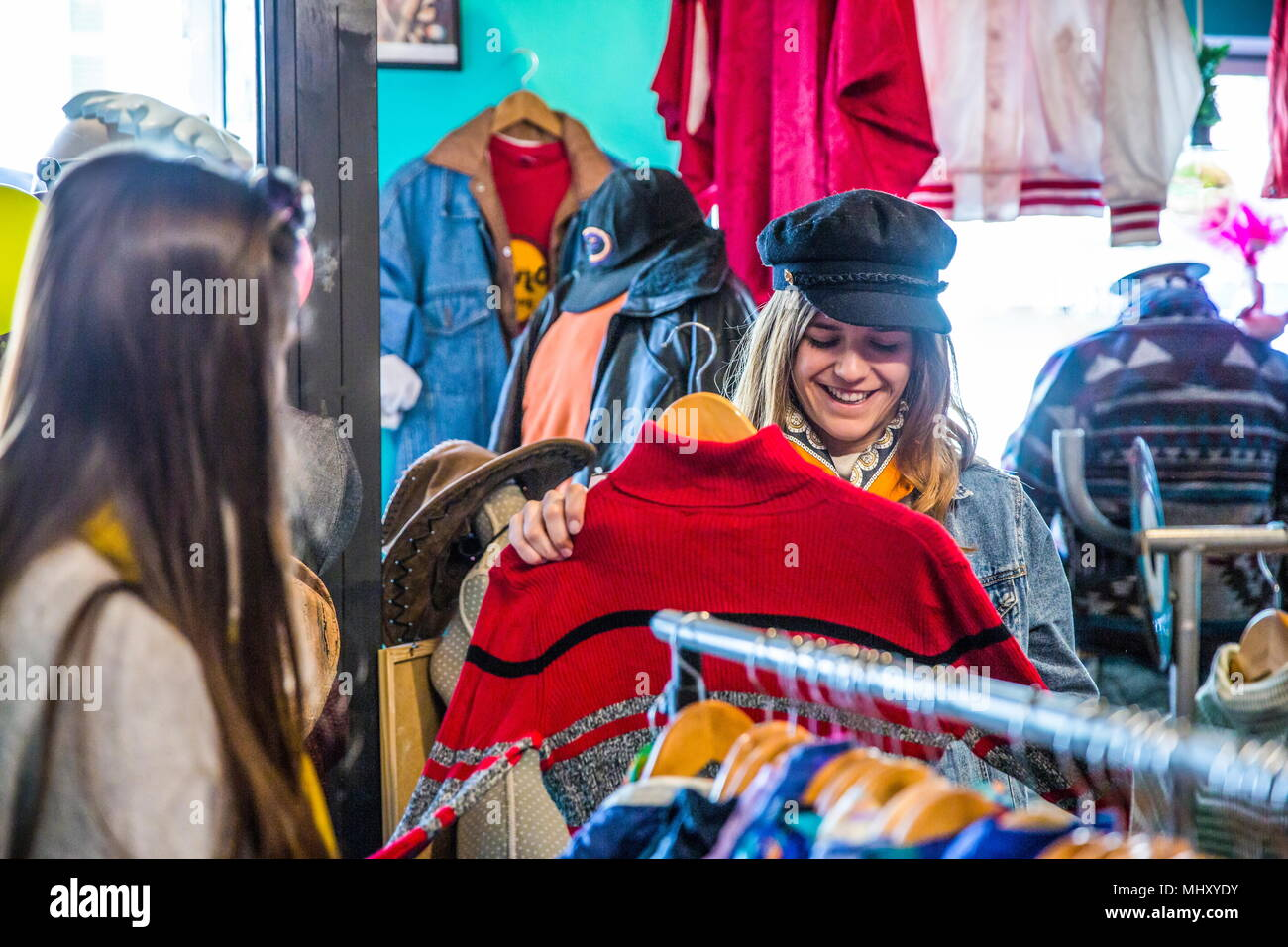 Friends browsing vintage clothes in thrift store - Stock Image