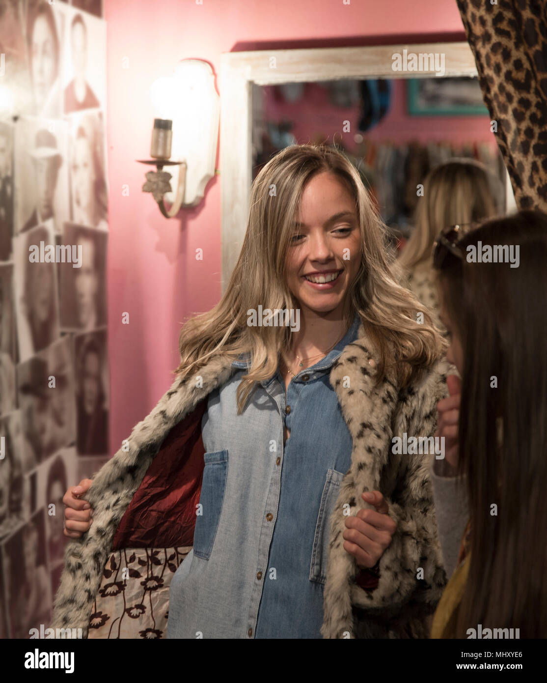 Young woman trying on vintage clothes in thrift store - Stock Image