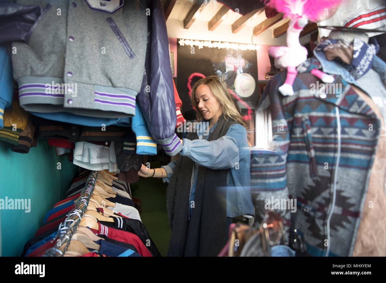 Young woman browsing vintage clothes in thrift store - Stock Image