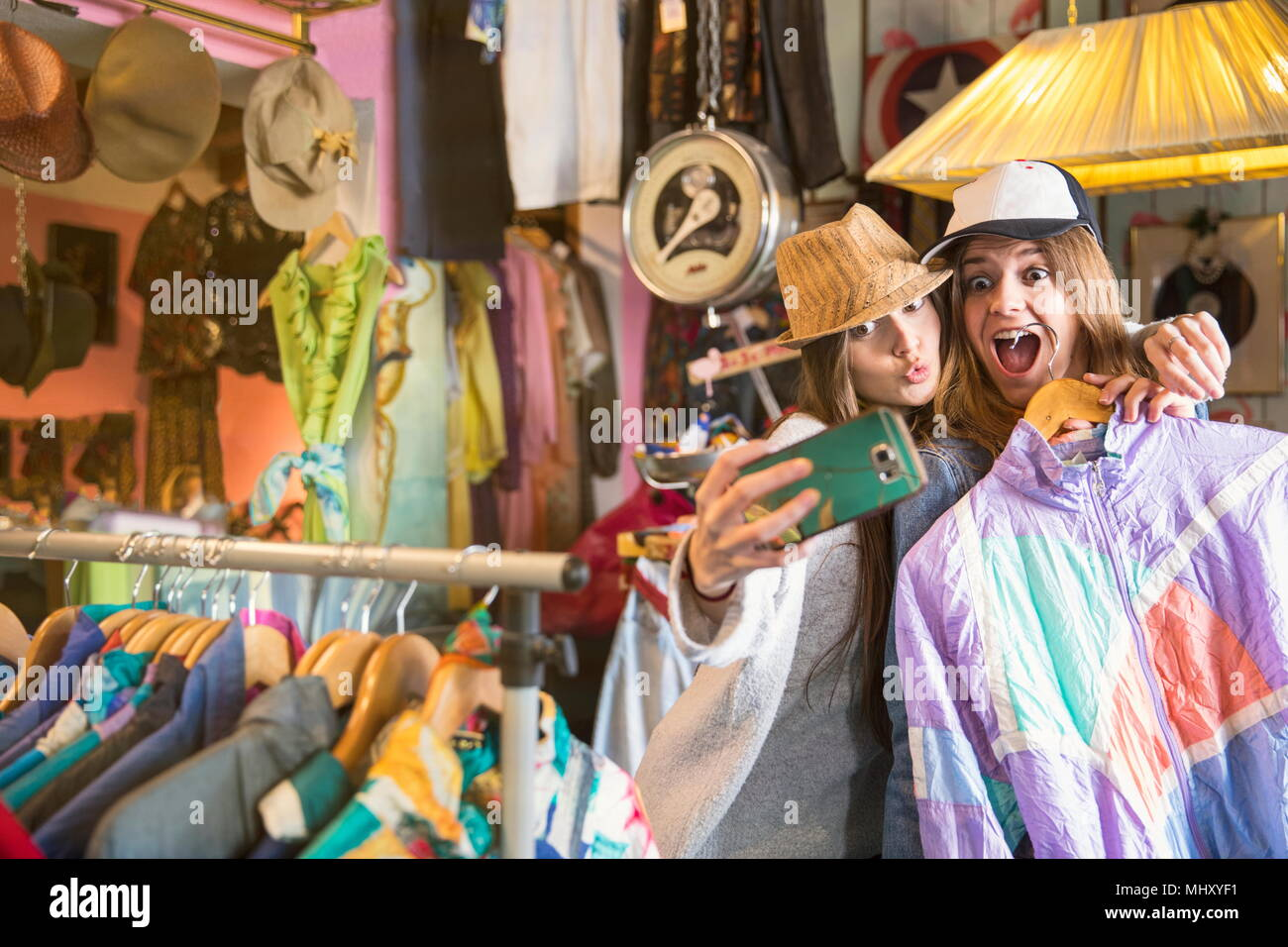 Friends taking selfie in thrift store - Stock Image