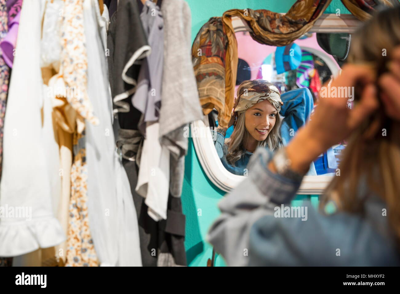 Mirror image of young woman trying on vintage clothes in thrift store - Stock Image