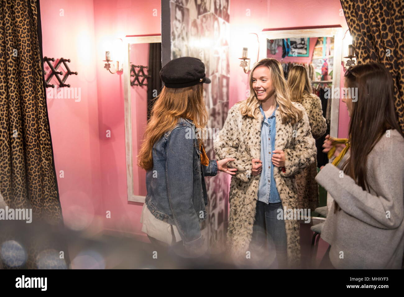 Friends trying on vintage clothes in thrift store - Stock Image