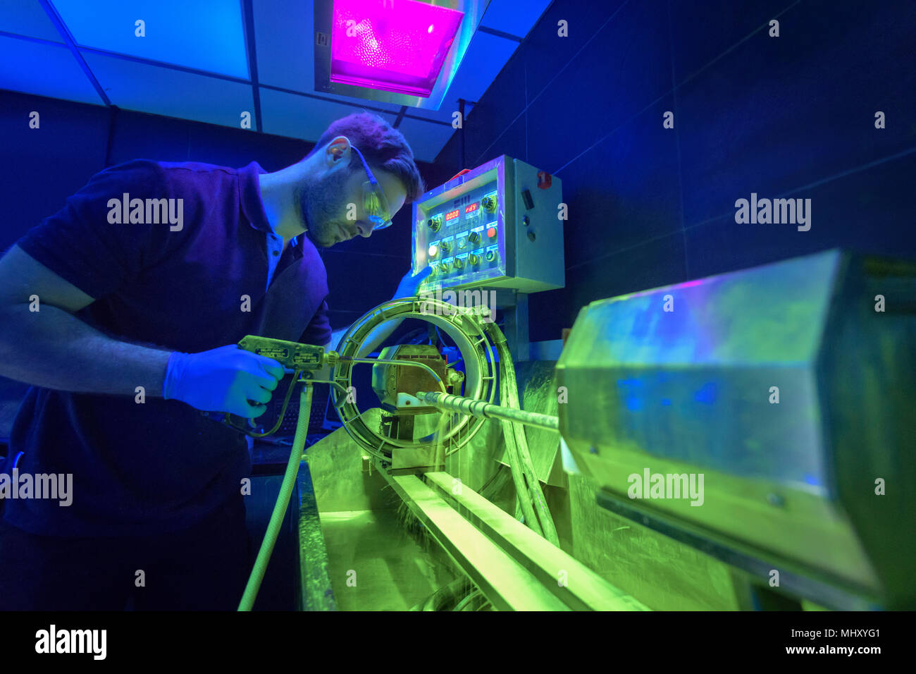 Worker using ultra violet light to detect cracks in electroplating factory - Stock Image