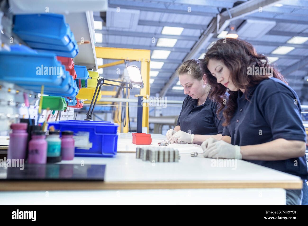 Female workers painting wax masking onto components in electroplating factory - Stock Image