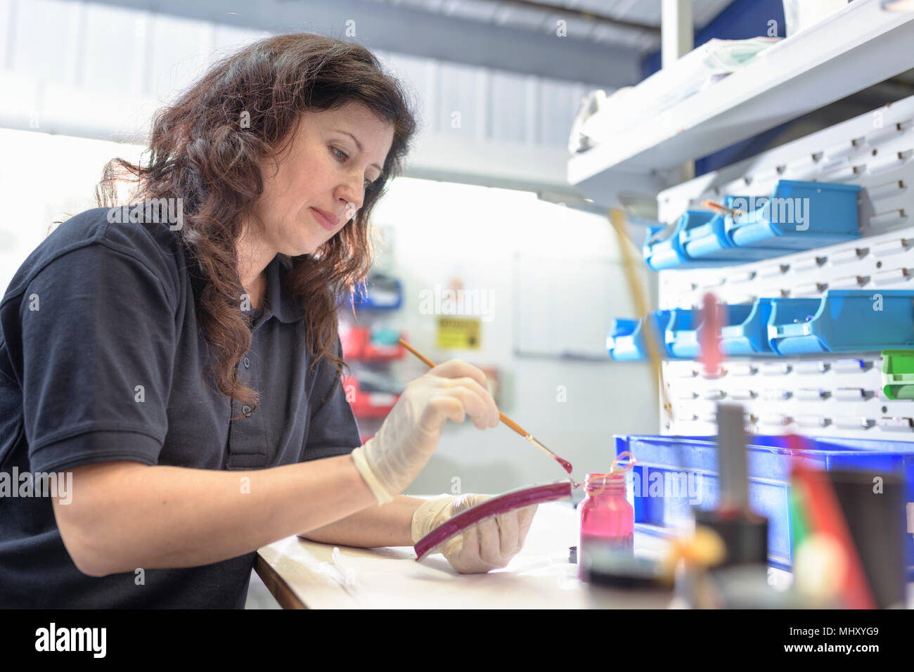 Female worker painting wax masking onto components in electroplating factory - Stock Image