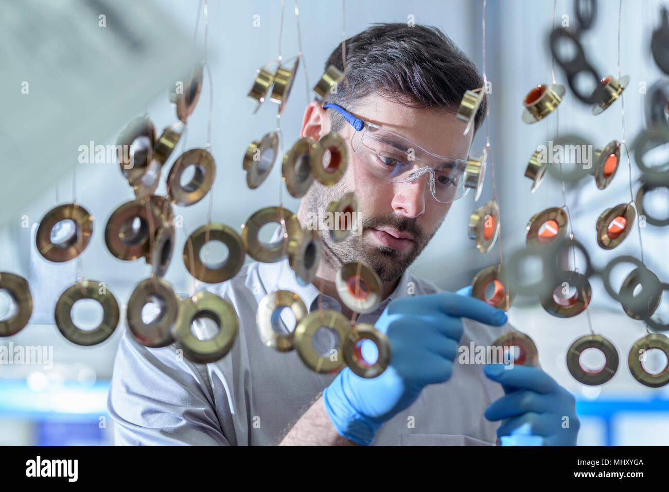 Worker hanging components ready to be dipped in chemicals in electroplating factory - Stock Image