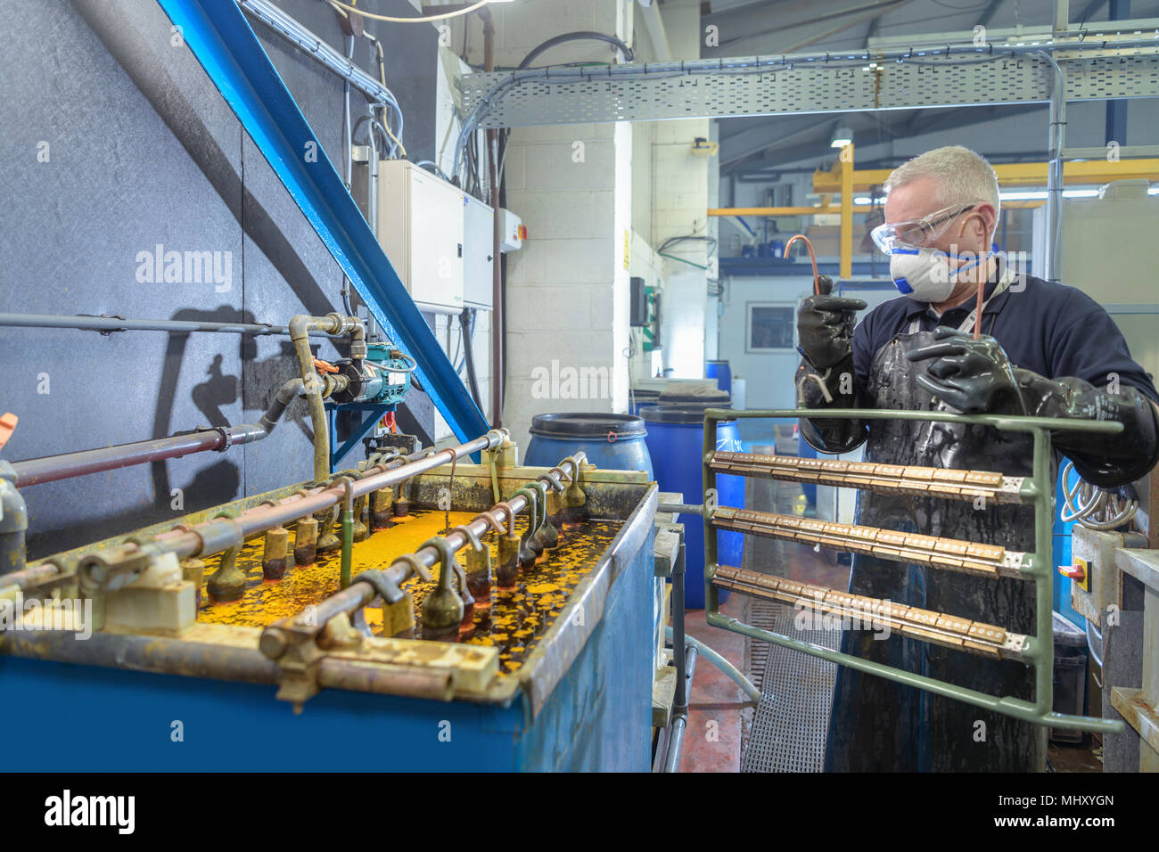 Worker placing components into chromium plating bath in electroplating factory - Stock Image