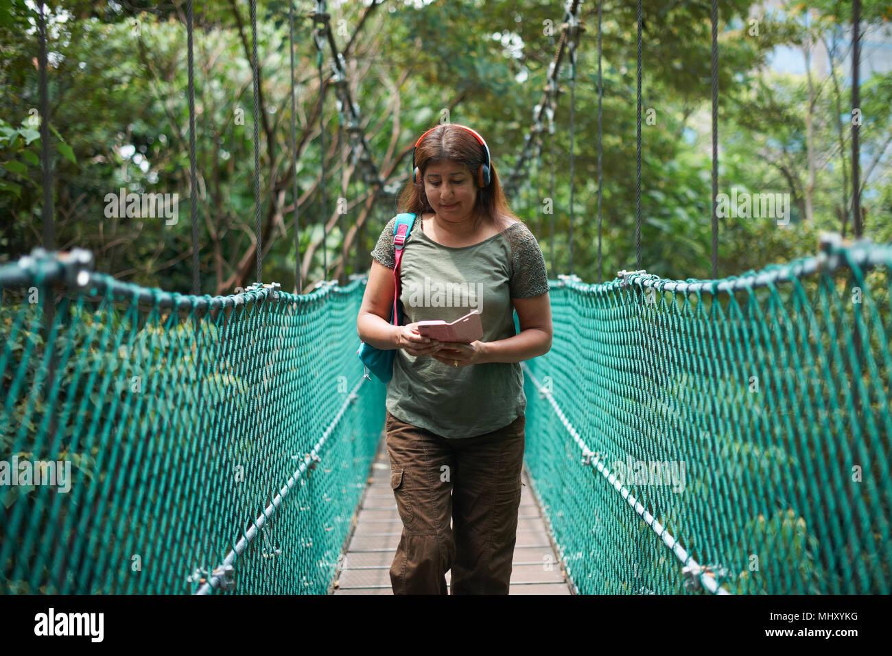 Tourist on bridge, KL Forest Eco Park, Kuala Lumpur, Malaysia - Stock Image