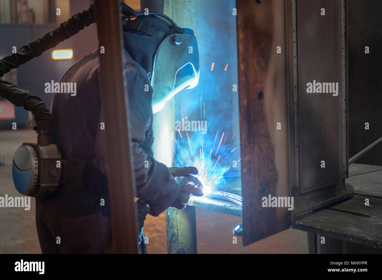 Welder welding part of digger bucket in engineering factory - Stock Image